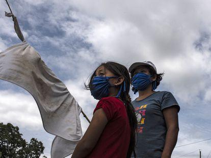Una mujer y su hija se encuentran en una carretera con una bandera blanca improvisada pidiendo comida durante la cuarentena obligatoria decretada por el gobierno contra la propagación de la covid-19 en San Luis Talpa, El Salvador, el 29 de mayo de 2020.
