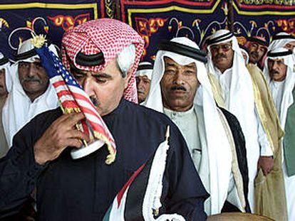 Un líder tribal de Jordania besa la bandera de EE UU antes de firmar en el libro de condolencias de la embajada de ese país en Ammán.