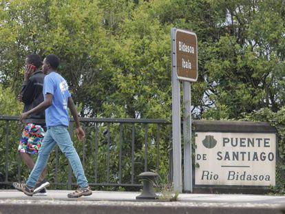 Dos extranjeros cruzan el puente de Santiago, en la frontera francoespañola en Irún (Gipuzkoa).