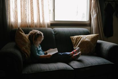 Una niña lee en el sillón.