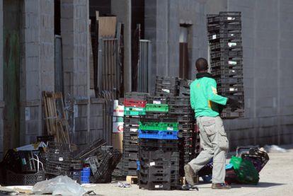Un joven apila los envases en la zona del almacenes donde se produce la venta de las cajas.