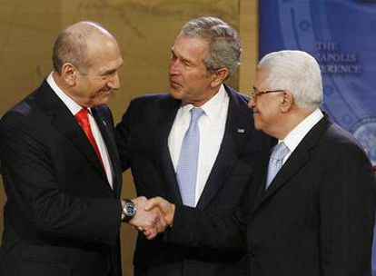 El primer ministro de Israel, Ehud Olmert (izquierda), estrecha la mano del presidente  palestino, Mahmud Abbas (derecha), en presencia de George W. Bush.