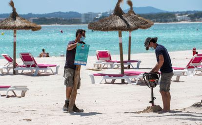 Dos trabajadores colocan un cartel informativo en la playa de Alcúdia, en Mallorca, el 12 de mayo.