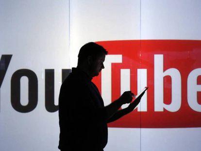 Un hombre pasa por delante del logo de YouTube.