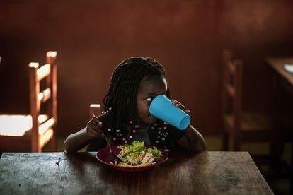 Una niña almuerza en la 'escolinha' o escuela de educación infantil del barrio cuatro de Massaca, que tiene un total de seis. Este centro educativo, al que acuden 45 alumnos por ahora, fue inaugurado el pasado mes de mayo. Pincha en la imagen para ver la fotogalería completa.