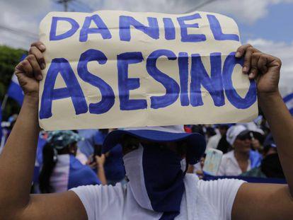 Una manifestante sostiene un cartel contra el presidente Ortega.