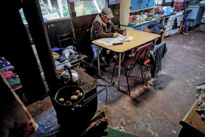 Un hombre de 63 años, se sienta en la cocina de su casa del campamento Pedro del Río Zanartu en Concepción, Chile.