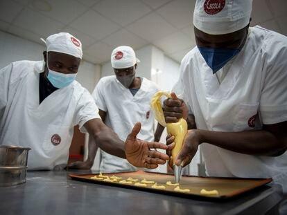 Moustapha Thiandoum, en el centro, junto a Abdoulaye Kande, con mascarilla azul, y Mamadou Diouf atienden al taller de formación en panadería que realizaron gracias a Nostos África para formarse y así poder volver a Senegal y montar su propia pastelería.