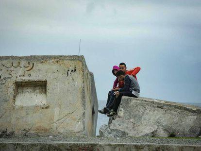 Tres menores sentados frente al mar en Ceuta, el pasado viernes.