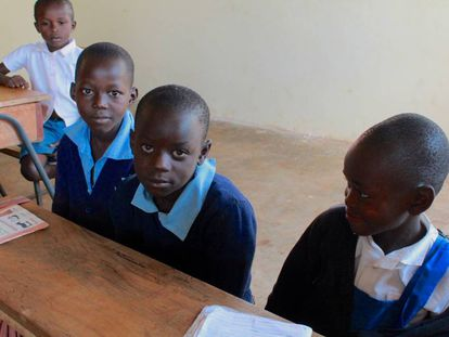 Byron, junto a sus dos compañeros de pupitre en la escuela de Kabondo.