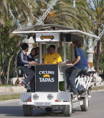 Unos turistas pasean por Barcelona sobre un 'bicibar'.