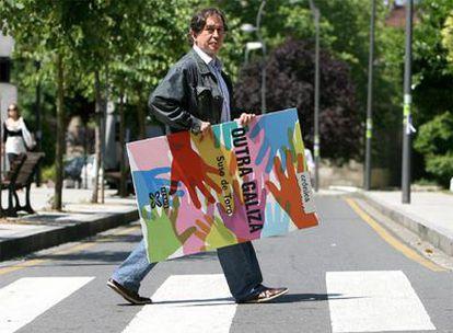 Suso del Toro, cruzando un paso de cebra próximo al campus de Santiago, con el cartel anunciador de su nuevo libro bajo el brazo.