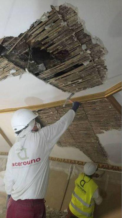 Dos trabajadores eliminan el falso techo y sacan a la luz el artesonado de la iglesia de Santa María la Blanca, en Canillejas.
