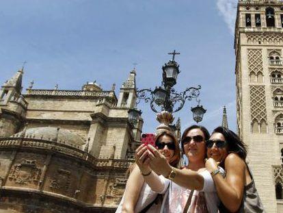 Turistas se fotografían con la Giralda y la Catedral de Sevilla.