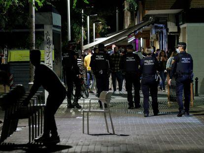 Agentes de la Policía Local de Valencia recorren las terrazas de una conocida zona de ocio para comprobar el toque de queda.
