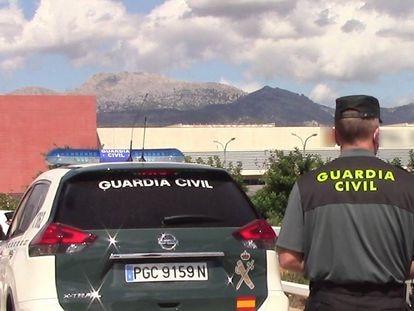 Un vehículo de la Guardia Civil y un agente de espaldas, en una imagen de archivo.