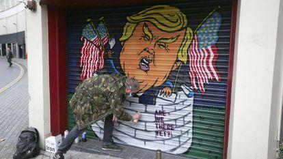 Jack Dones pinta un graffiti de Donald Trump en un comercio de la ciudad británica de Bristol.