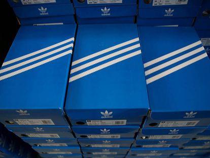 Cajas apiladas de zapatillas Adidas, con el diseño de las tres rayas.