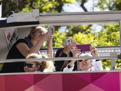 Turistas haciendo fotos a la Sagrada Familia desde un autobús.