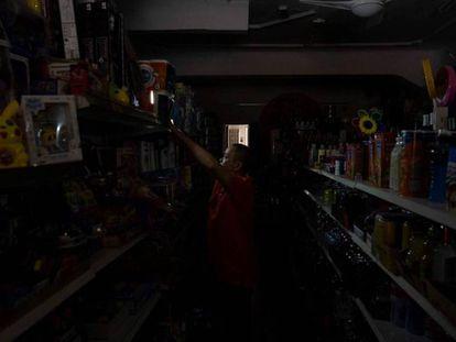 El dueño de una tienda en el centro de Santa Cruz coloca luces provisionales mientras espera que se restablezca el suministro eléctrico tras el apagón que ha afectado a toda la isla.
