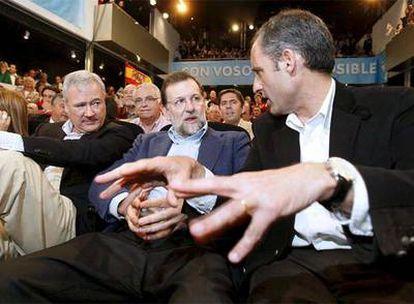El presidente del PP, Mariano Rajoy, junto a los presidentes regionales de su partido en la Comunidad Valenciana, Francisco Camps y Murcia, Ramón Luis Valcárcel, en el acto celebrado en Elche.
