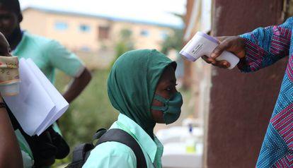 Toma de temperatura a un estudiante a las puertas de una escuela secundaria en Lagos (Nigeria):