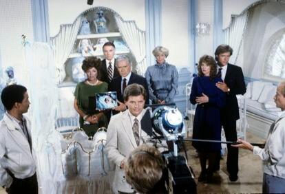 Blake Carrington (John Forsythe), con uno de sus impolutos trajes a medida, junto a Alexis (Joan Collins) muestran la foto de un bebé rodeados por el resto de la familia en una habitación de tules y molduras preparada para un bebé de alta cuna. |