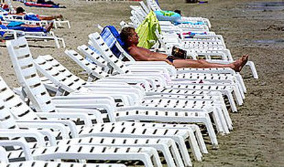 Un turista toma el sol en la playa D'en Bossa, de Ibiza.