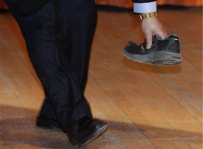 Un guardia de seguridad recoge el zapato lanzado al primer ministro chino, Wen Jiabao, mientras pronunciaba una conferencia en la Universidad de Cambridge (Reino Unido).