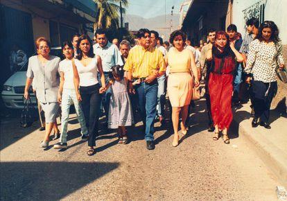 Evelyn Salgado Pineda (a la izquierda, con playera blanca) camina junto a su padre en un acto de campaña en los años 90.