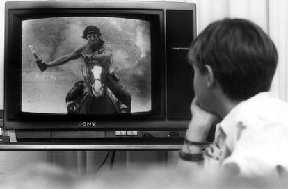 Un niño ve 'Rambo' en televisión en el comedor de su casa en 1993.