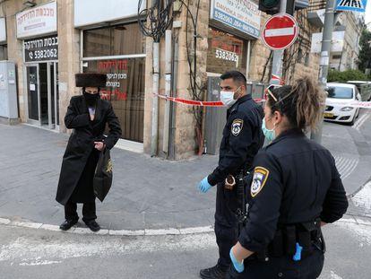 Dos agentes identifican a un ultraortodoxo en un acceso al barrio de Mea Shearim, el domingo en Jerusalén.