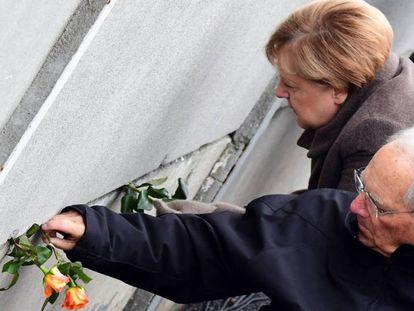 La canciller alemana, Angela Merkel, y el presidente del Bundestag, Wolfgang Schäuble, colocan rosas en una rendija del muro de Berlín durante la celebración del 30º aniversario.