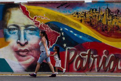 Una joven y una niña frente a un mural de Chávez.