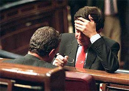 El diputado de CiU Ignasi Guardans habla con Jesús Caldera (de espaldas), durante el pleno.