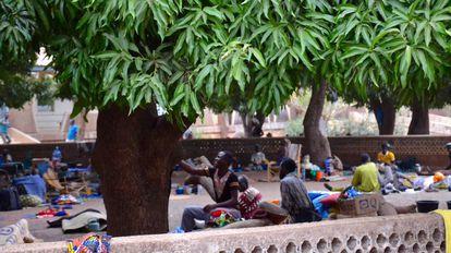 Familiares y enfermos esperan bajos los mangos en el hospital de Tanguiéta.