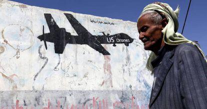 Un yemení pasa junto a una pared en Saná, capital de Yemén, en la que un grafiti protesta contra los ataque aéreos de EE UU.
