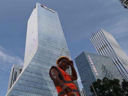 Un trabajador camina frente a las oficinas centrales de Evergrande, en Shenzhen, al sureste de China, en una imagen de archivo.