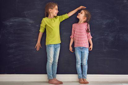 Dos niñas comparan su altura.