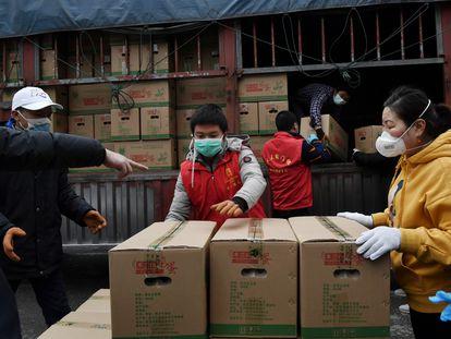 Un grupo de voluntarios descarga alimentos para un complejo de viviendas en Wuhan, el foco de la epidemia de coronavirus.