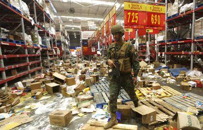 Un soldado chileno custodia un supermercado afectado por los saqueos, el pasado 22 de octubre.