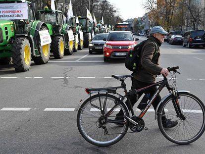Un hombre cruza una carretera con su bicicleta cerca de una línea de tractores que bloquea el parlamento en Kiev el 12 de noviembre de 2019