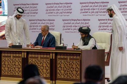 Los jefes de los equipos negociadores de EE UU y los talibanes durante la firma del acuerdo en Doha (Qatar).