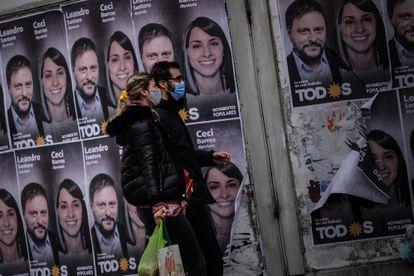 Una pareja camina frente a un cartel con la cara de Leandro Santoro, primer precandidato a diputado por el Frente de Todos, el 9 de septiembre de 2021, en la ciudad de Buenos Aires