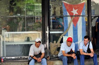 Tres hombres esperan la llegada del omnibús en La Habana, Cuba, hoy, martes 4 de enero de 2011