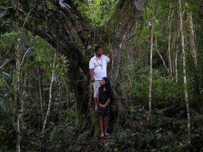 """Lázaro Kamlem, 47 años, cacique de la aldea de Palmeira, posa con su hija Ludmila, de 10, cerca de un árbol en la tierra indígena Xokleng Laklano, José Boiteux, estado de Santa Catarina, Brasil, el 20 de agosto de 2021. Kamlem es descendiente de Shaman Kamlem, el curandero de Xokleng que vaticinó en su lecho de muerte, en 1925, que perderían su tierra a manos de los """"hombres blancos"""", pero que algún día la recuperarían."""