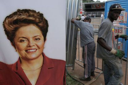 Unos operarios colocan un cartel de Dilma Rousseff en un acto de campaña
