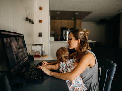 Una madre intenta trabajar con su hija encima.