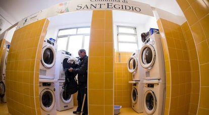 Un hombre mete ropa en una secadora en la lavandería inaugurada el lunes en Roma.