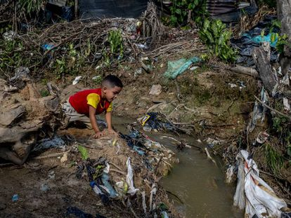 Un niño juega entre los escombros y el caño de aguas fecales del asentamiento 12 de septiembre, en Tibú, Colombia, a finales de agosto.